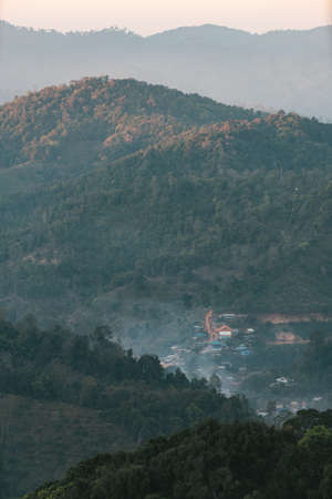 Village amid layers of mountain with sunlight and fog in the evening that view from the Akha village of Maejantai on the hill in Chiang Mai, Thailand. Standard-Bild - 122494084