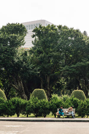 A couple sitting on stone seat with their dog in the park with pine trees in the background in the area of National Dr. Sun Yat-Sen Memorial Hall in Taipei, Taiwan. Standard-Bild - 122497374