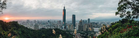 Aerial panorama over Downtown Taipei with Taipei 101 Skyscraper with trees on mountain in foreground in the dusk from Xiangshan Elephant Mountain in the evening. Фото со стока