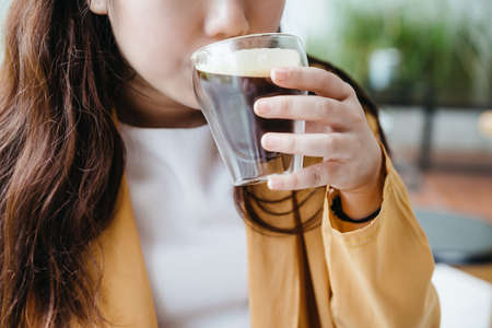 Woman wearing yellow jacket sipping Frothy Nitro Cold Brew Coffee in drinking glass with green blur background. Standard-Bild - 122497378