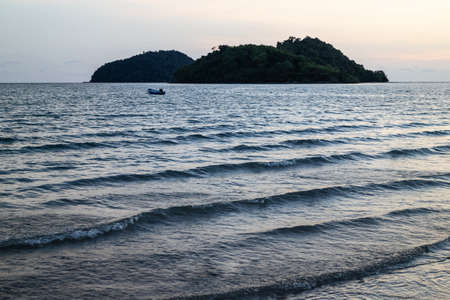 Green islands and reflected sea wave with blue, yellow sky color in background in the evening in Koh Mak Island at Trat, Thailand. Standard-Bild - 122497667