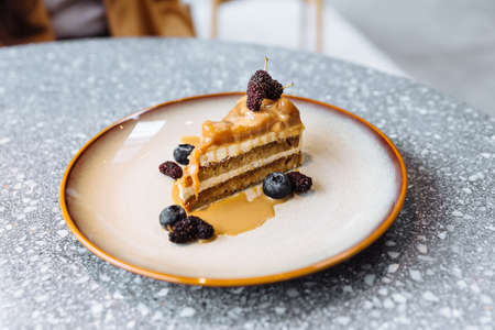 A slice of coffee caramel cake topping with caramel sauce, blueberry and raspberry in plate in granite top table. Standard-Bild - 122497675