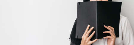 Muslim woman wearing hijab, white shirt and holding a black cover book in front of her on the right side with copy space. Standard-Bild - 122497679