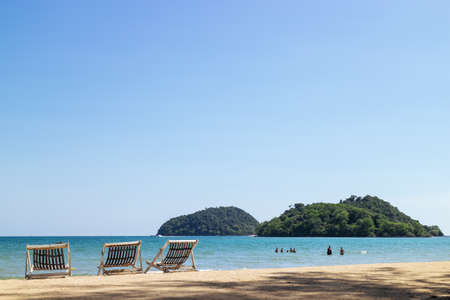 Three folding beach chairs on the beach with sea and bright sky in the background at Koh Mak in Trat, Thailand. Seasonal Vacation. Background with copy space. Standard-Bild - 122497842
