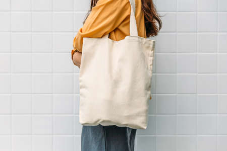 Woman is holding bag canvas fabric for mockup blank template. Standard-Bild - 122497843