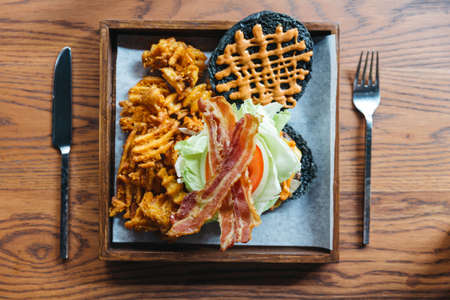 Top view of charcoal cheese burger with crunchy bacon, cabbage, onion, tomato, thousand island sauce and waffle fries. Served with knife and fork on wooden table. 版權商用圖片