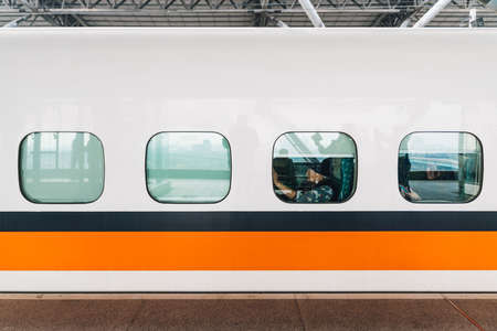 Side view of Taiwan High Speed Train, White train with orange and blue stripe with passengers sitting near window stop on platform in Taiwan, Taipei. Zdjęcie Seryjne