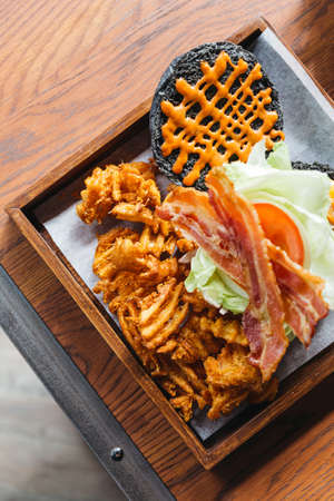 Top view of charcoal cheese burger with crunchy bacon, cabbage, onion, tomato, thousand island sauce and waffle fries. Served with knife and fork on wooden table. Stok Fotoğraf