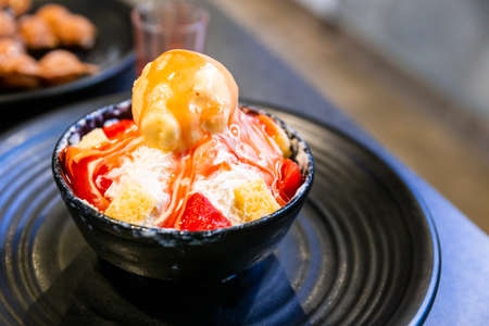 Bingsu, a Korean shaved ice dessert with sweet toppings such as vanilla ice cream, cheese cube and sweetened condensed milk. It's very popular dessert. 免版税图像