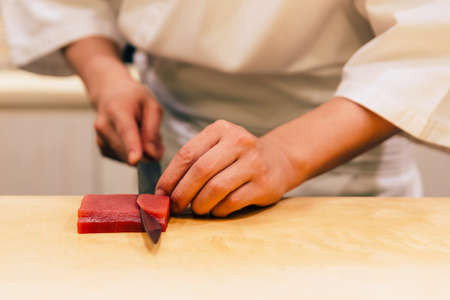 Japanese Omakase Chef cut bluefin tuna (Otoro in Japanese) neatly by knife on wooden kitchen counter for making sushi. Japanese luxury meal.