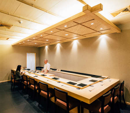 Japanese Omakase Restaurant that decorated mostly with wood. Chef cooking in kitchen counter and directly serve to customer. 新聞圖片