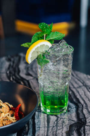 Iced Apple Soda with sliced lemon and mint leaves in drinking glass on marble top table. Imagens