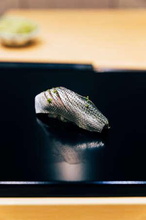 Japanese Omakase Menu: Saba Sushi (Mackerel) sprinkle with minced Yuzu peel on glossy black plate. Japanese luxury meal.