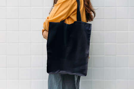 Woman is holding black bag canvas fabric for mockup blank template.