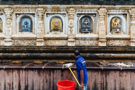Homme de concierge nettoyant le mur du temple décoré de nombreuses formes et cultures de statues antiques de Bouddha au temple Mahabodhi à Bodh Gaya, Bihar, Inde. Banque d'images
