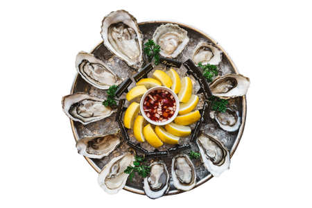 Isolated top view many kinds of Fresh Oysters served in round tray with slice lemon and spicy sauce.