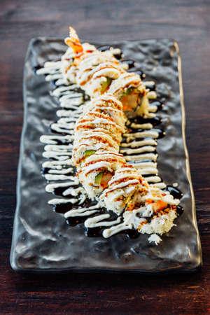 Maki Sushi with Rice, Shrimp Tempura, Avocado and Cheese inside covered Crispy Tempura Flour. Topping with Teriyaki Sauce and Mayonnaise. Stock Photo