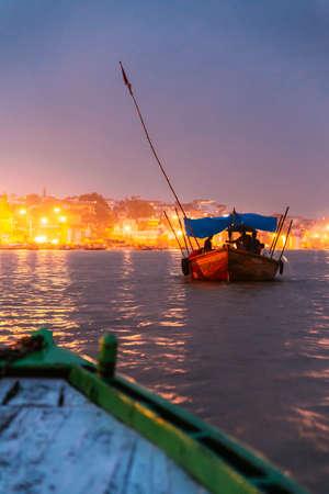 People on the boat floating on the river are going to pray at Varanasi Ganga Aarti at holy Dasaswamedh Ghat, near Kashi Vishwanath Temple, Varanasi, India.