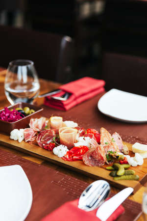 Cold cuts on wooden board with prosciutto, bacon, salami and sausages. Meat platter appetisers served with pickle and olives on dining table with cutlery.