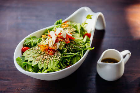 Japanese salad with avocado, tomato, green oak, almond and sesame topping sesame salad dressing. 스톡 콘텐츠
