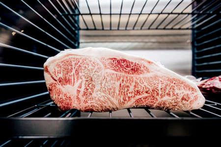 Premium Rare Sirloin Wagyu A5 beef with high-marbled texture inside refrigerator.
