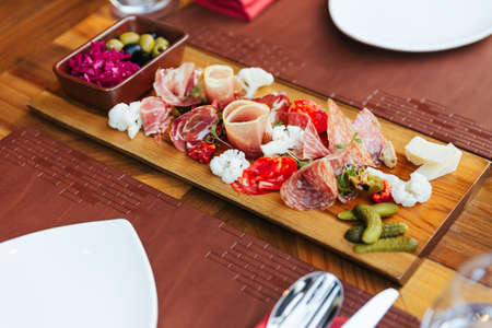 Cold cuts on wooden board with prosciutto, bacon, salami and sausages. Meat platter appetizers served with pickle and olives on dining table with cutlery.