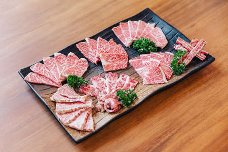 Premium Rare Slices many parts of Wagyu A5 beef with high-marbled texture on stone plate served for Yakiniku (Grilled Meat).