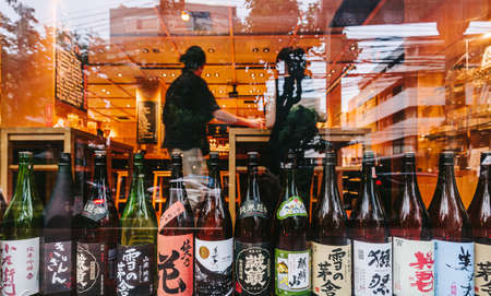 Many major and minor brands of Japanese liquors are including beer, sake, spirits and umeshu in front glass window of Japanese restaurant.