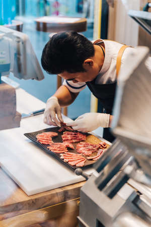 Asian butcher is arranging premium rare slices many parts of Wagyu A5 beef with high-marbled texture on stone plate in kitchen. Served for Yakiniku (Grilled Meat). Redactioneel