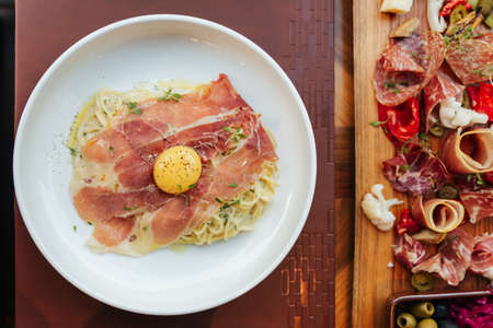 Top view of Fettuccine Carbonara with parma ham and yolk with black pepper. Served in white plate with Cold Cuts.