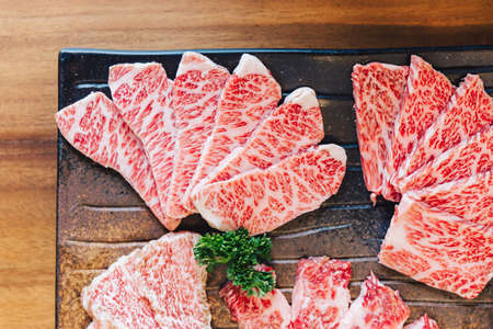 Close-up top view of Premium Rare Slices many parts of Wagyu A5 beef with high-marbled texture on stone plate served for Yakiniku (Grilled Meat). Banco de Imagens