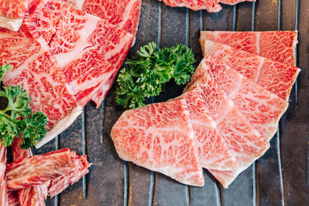 Close-up top view of Premium Rare Slices many parts of Wagyu A5 beef with high-marbled texture on stone plate served for Yakiniku (Grilled Meat). Stock fotó
