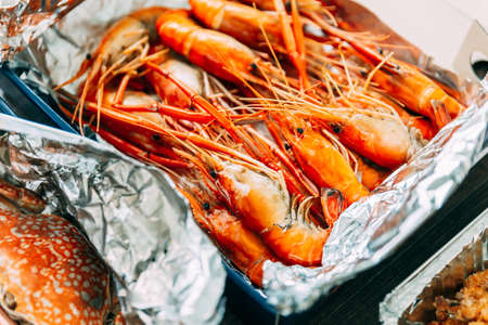 Above view of Thai grilled prawns (shrimps) in the shell in paper box that wrap with foil paper.