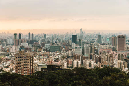 Aerial panorama over Downtown Taipei with layers of mountain in background in the dusk from Xiangshan Elephant Mountain in the evening.