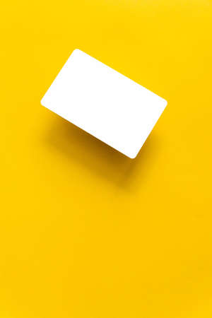 Top view of empty white business card with shadow on yellow paper background with copy space.