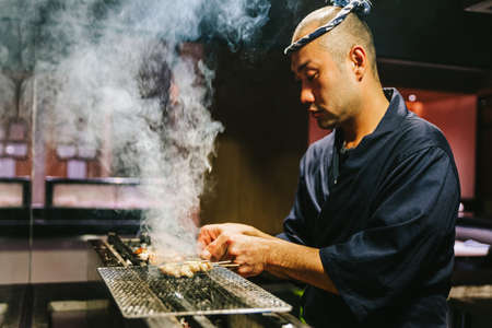Japanese Yakitori Chef is grilling chicken marinated with ginger, garlic and soy sauce with a lot of smoke.
