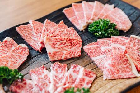 Close-up Premium Rare Slices viele Teile von Wagyu A5 Rindfleisch mit hochmarmorierter Textur auf Steinplatte serviert für Yakiniku (gegrilltes Fleisch).