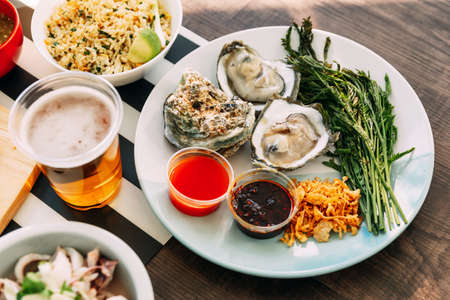 Fresh Oyster in shell in hand that served with fried shallot, chili paste, Acacia Pennata and Thai style seafood sauce. Thai style eating.