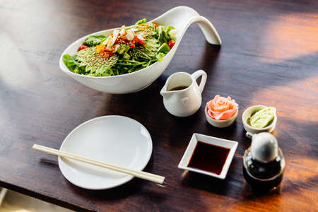 Japanese salad with avocado, tomato, green oak, almond and sesame topping sesame salad dressing. Served with pickled ginger and wasabi.