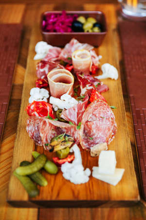 Cold cuts on wooden board with prosciutto, bacon, salami and sausages. Meat platter appetizers served with pickle and olives on dining table.