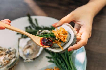 Ostrica fresca con guscio in mano che guarnisce con scalogno fritto, pasta di peperoncino, Acacia Pennata e salsa di frutti di mare in stile tailandese. Archivio Fotografico