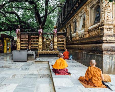 Indian Buddhist monk in meditation near The Bodhi Tree near Mahabodhi Temple while raining at Bodh Gaya, Bihar, India.