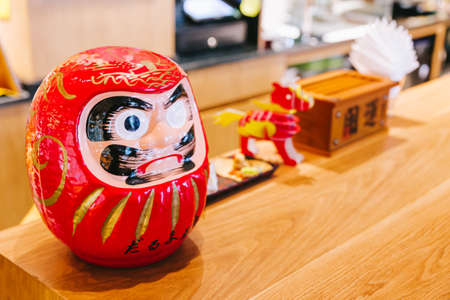 Daruma doll (Japanese traditional doll) on wooden counter with copy space.
