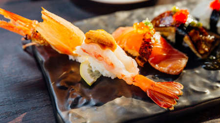 Premium Sushi Set include Deep fried Shrimp with Sea Urchin, Foie Gras, Salmon and Engawa on The Black Stone Plate served with wasabi and pink pickled ginger. Close-up on Shrimp Sushi.