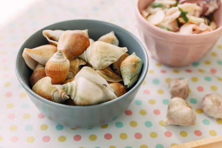 Grilled Laevistrombus Canarium in shells in wooden bowl served with Thai spicy seafood sauce.