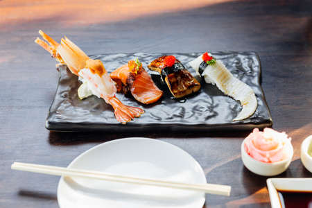 Premium Sushi Set includes Deep Fried Shrimp with Sea Urchin, Foie Gras, Salmon and Engawa on The Black Stone Plate served with wasabi and pink pickled ginger.