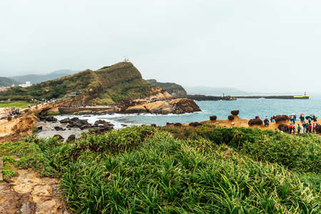 Aerial view diversity of tourists walking in Yehliu Geopark, a cape on the north coast of Taiwan. A landscape of honeycomb and mushroom rocks eroded by the sea. Фото со стока