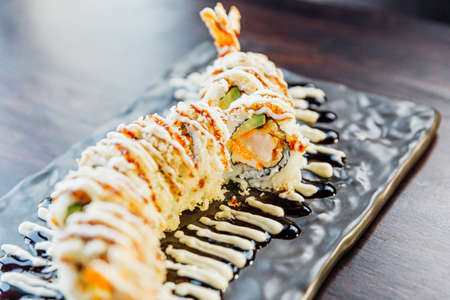 Close-up Maki Sushi with Rice, Shrimp Tempura, Avocado and Cheese inside covered Crispy Tempura Flour. Topping with Teriyaki Sauce and Mayonnaise.