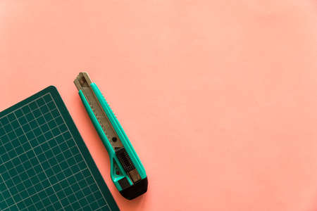 Top view of green rubber cutting mat with green cutter on the left side over pink color paper background. Background with copy space.
