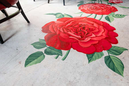 Painted roses with leaves on concrete floor. Interior restaurant decoration.